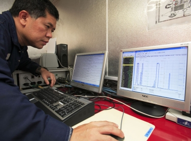 The Stena Clyde drilling rig at the Puffin 7 hole. Oil energy exploration industry. James Jie, Expro Data Aquisition engineer examines flow rates on laptop. Photographer: David Hancock. Copyright: SkyScans