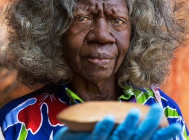 Madjedbebe habitation site has been dated by archeologists to have been occupied for 65,000 years, the longest of any site in Australia - traditional owner Simon Mudjandi (young man), holds up ancient axe head while May Nango (female grey hair) looks on