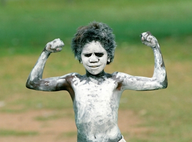 """Young Aboriginal boy painted with """"gupung"""" or white clay, ready for ceremony Photographer: David Hancock. Copyright: SkyScans."""