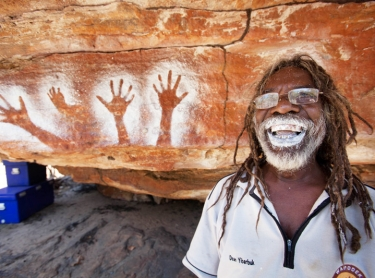 Kids and Dean Yibarbuk doing spray stencils at Kundjorlomdjorlom. Lofty lived in cave here as a child and young adult. He painted picture of female antilopine kangaroo with bent finger hand stencil for same beast. Location of IPA eclaration ceremony. Mok clan estate or Mankungdjang (sugarbag dreaming)Warddeken IPA Arnhem Land plateau indigenous land management Aboriginal culture indigenous rock art contact images