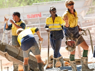 Wadeye community in northern Australia with local Aboriginal people showing housing infrastructure, employment, education, health and police initiatives. Concrete crew - Timothy Dora
