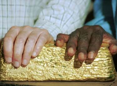 Aboriginal and non-Aboriginal hands on a gold ingot - Tanami mining venture, Central Australia. Photographer: David Hancock. Copyright: SkyScans.