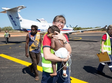The Royal Flying Doctor Service (RFDS) in Broome. Operations base, aircraft and staff working with patients in Broome and a medical clinic at Yakanarra near the Fitzroy River. Dr Nola McPherson carries ten month-old Marlon Macarthur off a RFDS Pilatus PC-12 aircraft after the baby boy was evacuated from a remote Kimberley community, to Broome. Accompanied by nurse Rachel Climpson and the boy's grandfather, Douglas Macarthur.