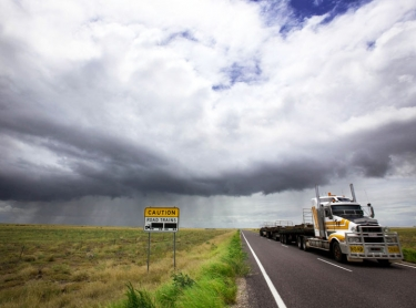 outback road in western queensland with looming storm in the wet season. weather storm sign road transport