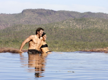 Tourists at Gunlom in southern Kakadu. tourism adventure travel couple water hole escarpment IHG Photographer: david hancock. Copyright: SkyScans.