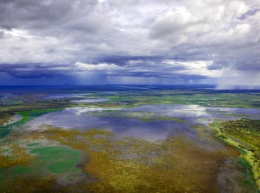 The Top End of Australia during the wet season flying in a helicopter, from the floodplains around the Adelaide River to Arnhem Land near the East Aligator River. Storms and rain over the floodplains - weather meteorology clouds wet season - south aligator floodplains