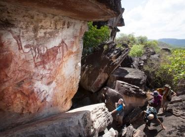 Venture North tourism on Cobourg Peninsula and through Arnhem Land. The tour takes visitors to the Garik Gunak Barlu national park, Oenpelli rock art sites at Karnbalunya and Mamukala in Kakadu NP. escarpment near Karnbarlunyah (Oenpelli) - rock art - Aboriginal guide Joey Nganjmirra shows tourists