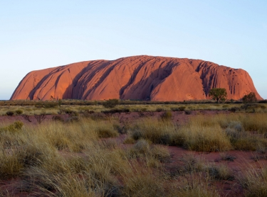 Uluru, also known as Ayers Rock, in central australia. Uluru Kata-Juta National Park attracts many tourists to the central desert and the rock is photographed and explored by people. NT